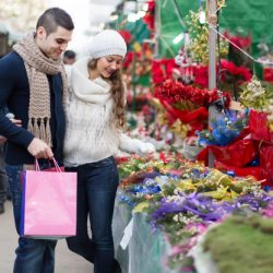 Charming girl with boyfriend choosing red flower at Christmas fair. Selective focus