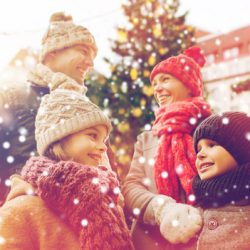 family, christmas, holidays, season and people concept - happy family over city background and snow