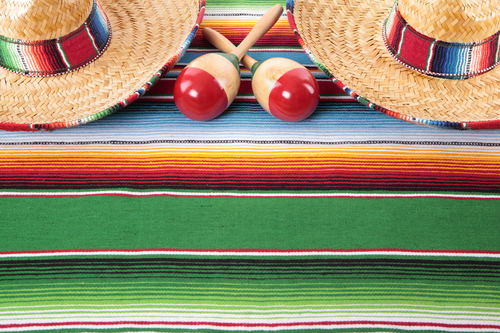 Mexican sombreros and maracas on a traditional serape blanket.  Space for copy.